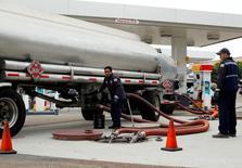 Imagen de archivo de unos trabajadores cargando combustible en una gasolinera de Encinitas, EEUU, oct 8, 2012. Los precios al consumidor de Estados Unidos registraron en septiembre su mayor caída en ocho meses al bajar el costo de la gasolina, pero un persistente aumento en los precios de otros productos y servicios sugirió que la inflación está encaminada a subir.   REUTERS/Mike Blake