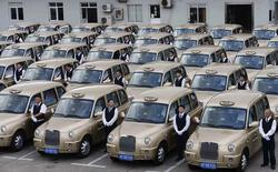 """Drivers stand next to brand new Geely Englon TX4 taxis, which were created based on the """"London cab"""", during an inauguration ceremony in Shanghai, October 11, 2014. REUTERS/Stringer"""