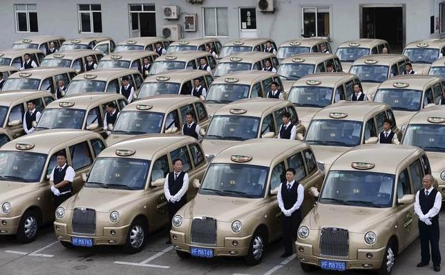 Drivers stand next to brand new Geely Englon TX4 taxis, which were created based on the ''London cab'', during an inauguration ceremony in Shanghai, October 11, 2014. REUTERS/Stringer