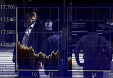 Un hombre se refleja en un tablero electrónico que muestra el índice Nikkei, afuera de una correduría en Tokio, Japón, 29 de septiembre de 2015. La mayoría de las bolsas de Asia cedía el martes, lastradas por un declive en los precios de las materias primas luego del reporte de unos datos débiles de crecimiento en China. REUTERS/Issei Kato