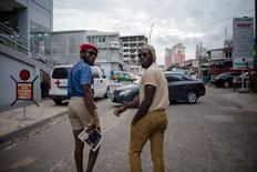 Fashion stylist Daniel Quist (L) and DJ Evans Kissi look back at the photographer as they walk down a street in Accra, Ghana, June 10, 2015. Young artists in Ghana's capital have evolved a new style that is turning heads and challenging accepted notions of African fashion.  REUTERS/Francis Kokoroko