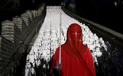 "A fan dressed as an Imperial Royal Guard character from ""Star Wars"" poses for a photo in front of five hundred replicas of Stormtroopers at the Juyongguan section of the Great Wall of China during a promotional event for ""Star Wars: The Force Awakens"" film, on the outskirts of Beijing, China, October 20, 2015. REUTERS/Jason Lee"