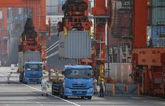 Workers load containers onto trucks from a cargo ship at a port in Tokyo, Japan, October 20, 2015. REUTERS/Toru Hanai
