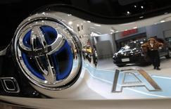 A visitor is reflected in a logo of Toyota Motor Corp at the company's showroom in Tokyo February 4, 2015. REUTERS/Yuya Shino