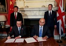 El secretario de Negocios del Reino Unido, Sajid Javid (al frente a la derecha) y el ministro de Comercio de China, Gao Hucheng, firman un acuerdo, junto al primer ministro británico, David Cameron (atrás a la derecha) y el presidente de China, Xi Jingping, en Londres, 21 de octubre de 2015. El presidente de China, Xi Jinping, firmó el miércoles un acuerdo multimillonario para financiar plantas nucleares en Gran Bretaña, en una visita que el primer ministro David Cameron espera que abra una ola de inversiones desde la segunda economía más grande del mundo. REUTERS/Suzanne Plunkett