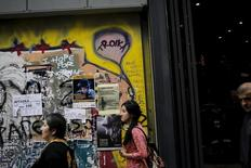 "People walk along the commercial Ermou street next to graffiti reading ""Troika"" in central Athens, Greece, October 20, 2015. REUTERS/Alkis Konstantinidis"