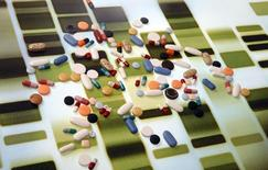 Pharmaceutical tablets and capsules are arranged on a background printed with a DNA pattern in this picture illustration taken in Ljubljana August 20, 2014. Picture taken August 20.      REUTERS/Srdjan Zivulovic