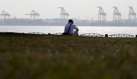 Мужчина сидит на берегу недалеко от грузового порта в Токио. 20 октября 2015 года. Замедление китайской экономики, второй крупнейшей в мире, ослабляет рост в Северной Азии и подталкивает некоторые страны к рецессии. REUTERS/Toru Hanai