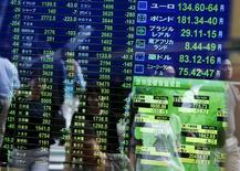 Peatones reflejados en un tablero electrónico que muestra la información de las acciones, en una correduría en Tokio, Japón, 29 de septiembre de 2015. Las bolsas de Asia reanudaban su declive el jueves luego de que una fuerte caída de las acciones chinas en la sesión previa reavivó las preocupaciones sobre la salud de la economía de ese país, y los inversores esperaban el resultado de una reunión del Banco Central Europeo. REUTERS/Issei Kato