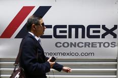 Una persona camina delante del logo de Cemex, en la Avenida de la Reforma, en Ciudad de México, 27 de agosto de 2014. La mexicana Cemex, una de las mayores cementeras del mundo, dijo el jueves que en lo que va del año logró una reducción de 710 millones de dólares en su deuda total y vendió activos por alrededor de 620 millones de dólares, como parte de su plan para recuperar su grado de inversión.  REUTERS/Edgard Garrido