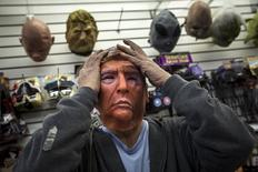 Employee Kenny Lomi adjusts a Halloween mask of Republican presidential candidate Donald Trump as he poses for a photo at the Village Party Store halloween headquarters in the Manhattan borough of New York, October 15, 2015. REUTERS/Andrew Kelly