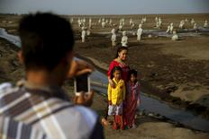 A man takes a picture of his family near stone sculptures of half-buried people at the Lapindo mud field in Sidoarjo, October 11, 2015. REUTERS/Beawiharta