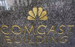 The NBC logo and Comcast are displayed on 30 Rockefeller Plaza, formerly known as the GE building, in midtown Manhattan in New York July 23, 2015. REUTERS/Brendan McDermid