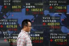 Un hombre camina delante de un tablero electrónico que muestra los índices de mercado de varios países, afuera de una correduría en Tokio,  Japón, 23 de octubre de 2015. Las bolsas de Asia caían el martes luego de que un repunte de cuatro semanas perdió fuerza antes de las reuniones de los bancos centrales de Estados Unidos y Japón esta semana, mientras que unas decepcionantes ventas de viviendas estadounidenses pesaban sobre el dólar. REUTERS/Toru Hanai