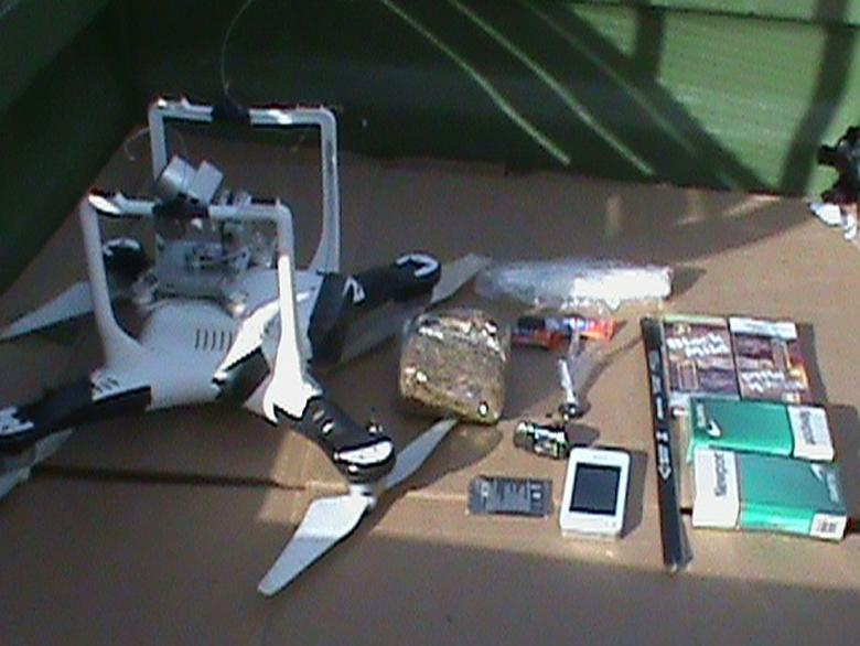 A drone that was carrying a package that contained two hacksaw blades, a cellphone, a cellphone battery, two packages of cigarettes, a hands-free device, two packs of cigars, super glue, a 5.3-ounce bag of marijuana, a 0.8 ounce bag of methamphetamine and a less than 1 gram bag of heroin, is pictured in this undated handout photo provided by the Oklahoma Department of Corrections.  REUTERS/Oklahoma Department of Corrections/Handout via Reuters