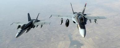 """Американские палубные истребители F-18E Super Hornet летят над Ираком во время операции против ИГИЛ. 4 октября 2014 года. США и союзники нанесли 14 новых авиаударов по позициям """"Исламского государства"""" в Ираке во вторник, в Сирии операций не проводилось, сообщил Пентагон в среду. REUTERS/USAF/Staff Sgt. Shawn Nickel/handout via Reuters"""