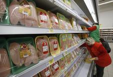 Работники магазина Ашан раскладывают продукты по полкам. Москва, 28 ноября 2014 года. Рост потребительских цен в России с 20 по 26 октября составил 0,2 процента, третью неделю подряд, сообщил Росстат. REUTERS/Sergei Karpukhin