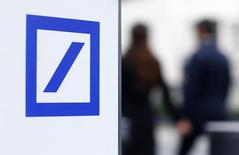 Pedestrians pass by a Deutsche Bank logo seen near the Deutsche Bank headquarters in Frankfurt, Germany October 8, 2015. REUTERS/Ralph Orlowski