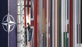 Рабочий устанавливает плакаты с флагами стран-членов НАТО у конгресс-центра в Страсбурге. 2 апреля 2009 года. Входящие в Североатлантический альянс государства обсуждают возможность наращивания своих сил вдоль российской границы, сообщила в среду Wall Street Journal со ссылкой на дипломатов и военных. REUTERS/Christian Hartmann
