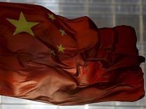 """La bandera de China ondea en un distrito comercial en Pekín, 29 de octubre de 2015. China aumentará """"significativamente"""" la participación del consumo en el crecimiento de la economía en los próximos cinco años, dijo el jueves una radio estatal, citando un comunicado difundido por el Partido Comunista en el cierre de una reunión que se realizó esta semana. REUTERS/Kim Kyung-Hoon"""