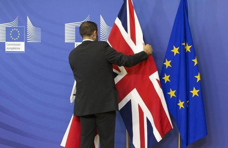 An employee at the European Commission adjusts a British flag ahead of the meeting between British Prime Minister David Cameron and European Commission President Jean-Claude Juncker in Brussels, October 15, 2015. REUTERS/Yves Herman