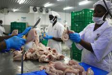 Funcionários cortando frango em Kampala, Uganda.   16/04/2015   REUTERS/James Akena