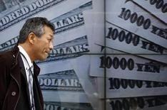 Un peatón camina junto a un tablero electrónico que muestra una foto de billetes de yen japonés y dólares estadounidense, afuera de una correduría en Tokio, 9 de enero de 2014. El yen se apreciaba el viernes, impulsado por la decisión del Banco de Japón de mantener sin cambios su política monetaria, mientras que el dólar retrocedía tras la divulgación de datos sobre el gasto del consumidor en Estados Unidos que arrojaron el menor avance en ocho meses. REUTERS/Yuya Shino