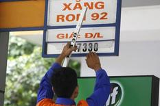 An employee changes a price sign at a petrol station in Hanoi, Vietnam September 3, 2015. REUTERS/Kham