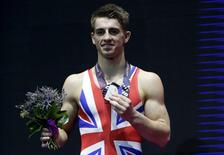 Britain's Max Whitlock celebrates his silver medal following the floor medals ceremony during the men's apparatus final at the World Gymnastics Championships at the Hydro arena in Glasgow, Scotland, October 31, 2015. REUTERS/Russell Cheyne