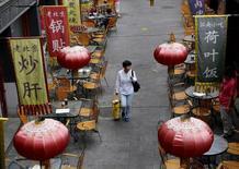 Una mujer pasea por un distrito comercial de Pekín. 22 de septiembre de 2015. El crecimiento del sector de servicios en China se enfrió en octubre, según un sondeo publicado el domingo, lo que sugiere que las presiones se están acumulando sobre la segunda economía del mundo pese a una serie de medidas de estímulo a la actividad. REUTERS/Kim Kyung-Hoon