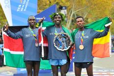 Geoffrey Kamworor (left) and Stanley Biwott (middle) and Lelisa Desisa pose for a photo following the Professional Men's division race at the 2015 TCS New York City Marathon. Mandatory Credit: Derik Hamilton-USA TODAY Sports