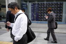 Personas miran sus celulares frente a un tablero electrónico que muestra la información de las acciones, en una correduría en Tokio, Japón, 23 de octubre de 2015. Las bolsas de Asia caían el lunes a su nivel más bajo en casi tres semanas por una toma de ganancias, luego de que el reporte de unas débiles encuestas de manufactura en China y los datos de gasto de los consumidores de Estados Unidos aumentaron las preocupaciones sobre las perspectivas económicas mundiales. REUTERS/Toru Hanai