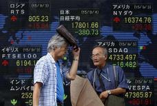 Un peatón que se cubre de la lluvia pasa delante de un tablero electrónico que muestra los índices de las acciones de varios países, afuera de una correduría en Tokio, Japón, 4 de septiembre de 2015. Las bolsas de Asia subían el martes ayudadas por el avance de los mercados en Estados Unidos y unos datos recientes que apuntan a que la economía mundial podría haber dado un giro decisivo, aunque la cautela de los bancos centrales sugiere que una recuperación podría no ser duradera. REUTERS/Yuya Shino