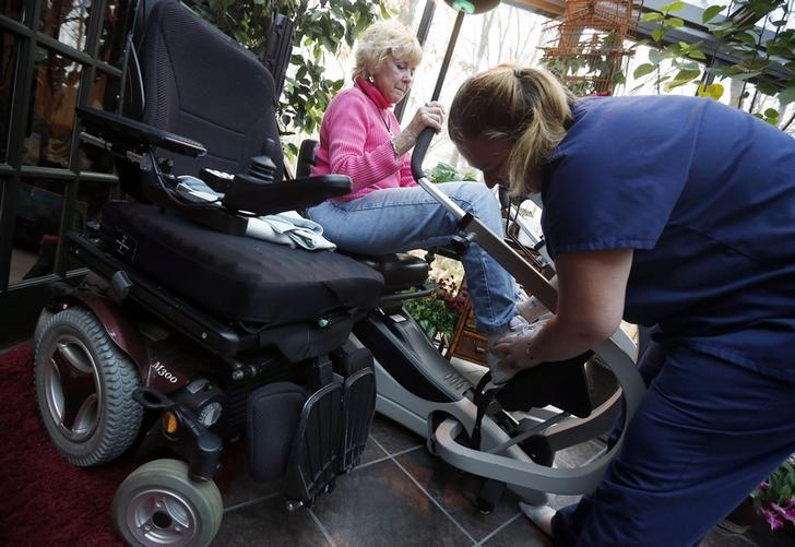 Sandy Wright (L) receives some help getting into her exercise bike from her C.N.A. (Certified Nursing Assistant) Jessica Haynes at her home in Peoria, Illinois, November 25, 2013.  REUTERS/Jim Young