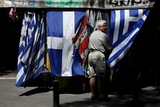 A man stands next to Greek national flag at a kiosk in central Athens, Greece, July 20, 2015. REUTERS/Yiannis Kourtoglou