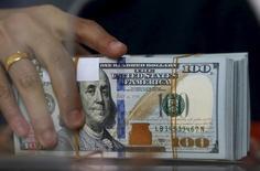 Un empleado sostiene un fajo de billetes de  100 dólares estadounidenses, en una casa de cambio en Yakarta, 8 de octubre de 2015. El dólar probablemente subirá contra otras monedas importantes en los próximos meses, a medida que los bancos centrales en Japón y la zona euro profundizan sus políticas monetarias ultra expansivas, mostró el jueves un sondeo de Reuters. REUTERS/Beawiharta