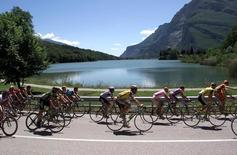 The pack of riders of the Giro D'Italia cycling race pass Lake Garda during the 20th 175 km stage from Predazzo to Madonna di Campiglio in this June 4, 1999 file photo. REUTERS/Stringer/Files