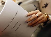 Журналист держит в руках отчет комиссии ВАДА на пресс-конференции в Женеве  9 ноября 2015 года. Независимая комиссия Всемирного антидопингового агентства рекомендовало дисквалифицировать Всероссийскую федерацию лёгкой атлетики за обширные допинговые нарушения. REUTERS/Denis Balibouse