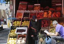 Un vendedor de fruta espera por clientes junto a un hombre que lee un diario, en una calle en Ciudad de México, 13 de agosto de 2014. La inflación interanual de México se moderó en octubre a un 2.48 por ciento y alcanzó un nuevo mínimo histórico, mostrando que una fuerte depreciación del peso tuvo poca presión sobre los precios al consumidor, según datos divulgados el lunes por el instituto nacional de estadísticas, INEGI. REUTERS/Henry Romero