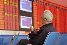 Un inversor frente a un tablero electrónico que muestra información bursátil, en una correduría en Fuyang, China, 8 de octubre de 2015. Las acciones chinas cayeron el martes después de que los valores de las firmas financieras se debilitaron, pero las pérdidas fueron limitadas por las perspectivas de reformas económicas y financieras. REUTERS/Stringer