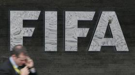 A reporter uses his cell phone as he walks past a FIFA logo in front of FIFA headquarters before a press conference of the FIFA Executive Committee in Zurich October 29, 2007.  REUTERS/Michael Buholzer