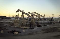 Imagen de archivo de una unidad de bombeo de crudo de Occidental operando cerca de Long Beach, EEUU, jul 30, 2013. La producción petrolera de Estados Unidos caerá más de lo esperado el año próximo, después de un desempeño sorpresivamente fuerte en 2015, mientras que la demanda será un poco más débil de lo estimado hace un mes, dijo el martes la Administración de Información de Energía.  REUTERS/David McNew