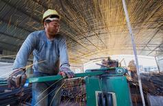 Un trabajador corta barras de metal en una construcción en Lianyungang, China, 12 de septiembre de 2015. El crecimiento de la producción industrial de China se moderó en octubre, mientras que las ventas minoristas subieron y la inversión se redujo, lo que revela unas presiones a la baja persistentes sobre la economía, que podría requerir un mayor apoyo político. REUTERS/China Daily