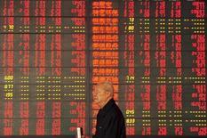 Un inversor camina delante de un tablero electrónico que muestra  información bursátil, en una correduría en Fuyang, China, 9 de octubre de 2015. Las acciones chinas cerraron el miércoles con un alza luego de que los inversores apostaron que Pekín ofrecerá un mayor estímulo, después de que una serie de datos dispares mostró que el crecimiento en la segunda economía más grande del mundo fue mediocre en el mejor de los casos. REUTERS/China Daily