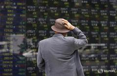 Un hombre mira un tablero electrónico que muestra información bursátil, afuera de una correduría en Tokio, 11 de mayo de 2012. Las bolsas de Asia retrocedían levemente el miércoles después de que una serie de datos dispares de China reveló un crecimiento apagado en la segunda economía más grande del mundo. REUTERS/Toru Hanai