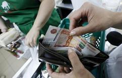 Женщина достает деньги из кошелька в магазине в Красноярске. 6 августа 2015 года. Несмотря на все еще высокие темпы роста цен на плодоовощную продукцию в России, сезонный фактор близок к завершению, что может вернуть прирост общего индекса потребительских цен в интервал 0,1-0,2 процента в неделю и ограничить годовую оценку уровнем 12,5 процента, пишут аналитики Росбанка. REUTERS/Ilya Naymushin