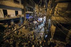 """Гражданские лица и военные осматривают место взрыва в Бейруте 12 ноября 2015 года. По меньшей мере 43 человека погибли и более 240 получили ранения в четверг в результате двух взрывов в густонаселённом южном пригороде Бейрута, бастионе ливанского движения """"Хезболла"""". Ответственность за взрывы взяла на себя группировка """"Исламское государство"""". REUTERS/Khalil Hassan"""