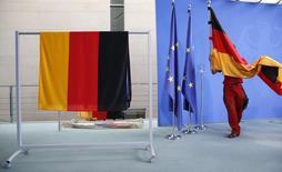 Funcionária colocando bandeira nacional da Alemanha antes de evento em Berlim.   07/09/2015   REUTERS/Fabrizio Bensch