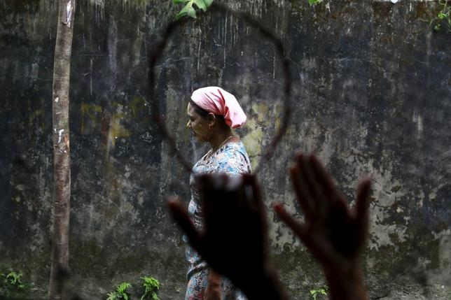 A Muslim Rohingya woman is seen through a fishing net while walking at a refugee camp in Sittwe October 29, 2015. REUTERS/Soe Zeya Tun