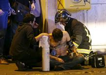 French fire brigade members aid an injured individual near the Bataclan concert hall following fatal shootings in Paris, November 13, 2015.  REUTERS/Christian Hartmann